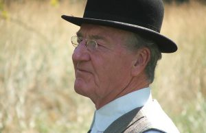 man wearing glasses and pioneer hat