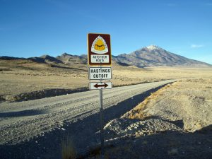 road sign with logo for Hastings Cutoff California Trail next to gravel road and mountains