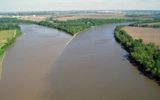 aerial overview of confluence of two rivers with light and darker colors