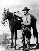 Artist William Henry Jackson wearing pioneer clothing and holding rifle standing next to a horse with bridle and saddle