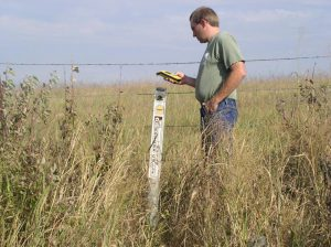 man checks GPS at trail marker in field with wire fence and tall grasses