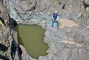 man sits next to water hole in rocky landscape