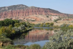 placid river flows through desert landscape with large red stone buttes in distance