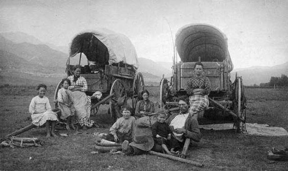 emigrant man, women and children sitting on and in front of two covered wagons