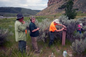 several people stand near trail marker made of railroad ties in sagebrush landscape