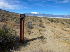 metal trail marker next to trail ruts and mountain in distance