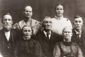 group of three men and four women wearing 19th century clothing