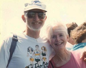 smiling woman and man wearing a ball cap and sunglasses