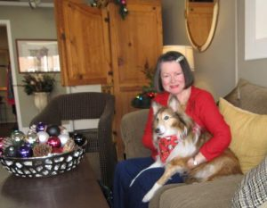 a woman sits on a couch in a living room holding a long haired dog