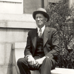 John G. Ellenbecker sitting outdoors on a bench